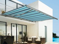 Blue striped awning on exterior of modern home. Perfectly covers outdoor seating area, and fits with minimalist aesthetic