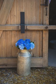 Milk Churn Filled With Blue Hydrangea Heads | Rustic Barn Wedding | Vintage Fairground Theme | Images by Something Clicked Photography | http://www.rockmywedding.co.uk/bryony-nick/