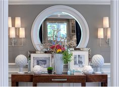 Grey wallpaper, wood console and wonderful white accessories. Love the mirror.