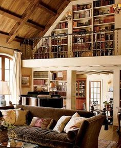 Wonderful living room+library - I wonder if there is a comfy chair up there for a reading corner?