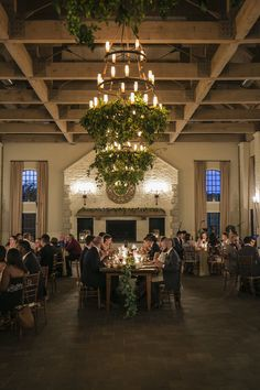 Stunning candlelit wedding reception space with hanging greenery on ceiling fixtures! Very cool for a summer or fall wedding! #weddingflowerssummer #receptionideas #greenery