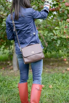 Wellesley & King   Every girl style on a budget. Click to see more fall outfit inspiration like this field jacket, plaid button up shirt, red hunter boots, classic COACH Court bag and distressed denim jeans.
