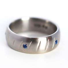 Custom men's wedding ring in palladium with blue sapphire accents. Custom wedding band by Abby Sparks Jewelry, custom jewelry designer in Denver, Colorado.
