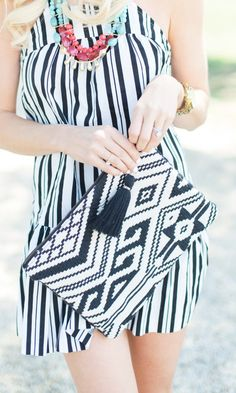 Black & white tribal-inspired woven clutch with a yarn tassel along the top zipper