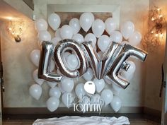 Silver foil letter balloons spell out LOVE in front of several white balloon bouquets for a fabulous photo backdrop at this elegant wedding   Balloons by Tommy   #balloonsbytommy