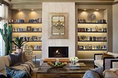 Bookshelf lighting produces a warm glow in this beautiful living room. Separated by a marble fireplace surround, the open shelves positively radiate under recessed lighting. A polished wood coffee table anchors the the chic seating area, while a thriving cactus adds height and a lively presence near the window.