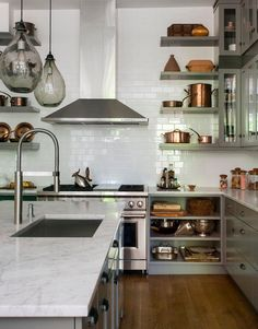 Love this but would go dark blue for cabinets French-inspired kitchen with honed Carrara marble countertops, handblown glass pendant lights, and Mauviel copper cookware to complement the white tile and 48-inch stainless steel Wolf range. From Interior designer Tanya Capaldo's gorgeously chic renovated 19th-century brownstone.