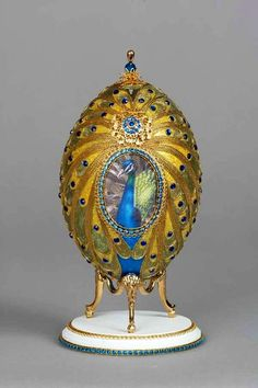 Superbly Decorated Greenish-Blue And Gold Peacock On Golden Fabergé Egg, Embellished With Sapphires And Other Blue Precious Stones.