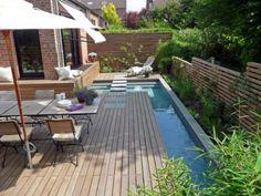 Quintal pequeno. Casas com corredores laterais podem aproveitar a idéia. Pequena piscina se estende ao longo do muro como um espelho d'água, junto ao canteiro de plantas. Além disso, cadeiras, espreguiçadeiras e mesa completam o ambiente.