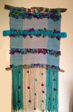 Telar decorativo tejido en lana, vellon peinado merino, lana con pelotitas en vellon peinado. Colores turquesa/calipso/gris/morado.  Mide 70 de ancho por 80 de largo, considerando los flecos mide 1,50 mt. Esta tejido con materiales de calidad y colgado en ramas de árbol.