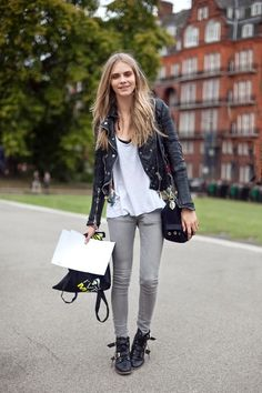 model Cara Delevigne in grey pants. combat boots. leather jacket. style.