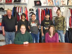 """The (New!) Burbank Family -   Back row: Head Honcho, Greg; Embroidery Machine Operator, Ivan; Master Embroidery Machine Operator, Jesus; Quality Control Manager, Mike; Machine Embroidery Operator, James.  Front row: Head Digitizer, Kent; Manager and Head of Sales, Kerri.   Stop on by and say, """"Hello!"""""""