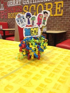 Easy diy centerpiece for comic book (Teen Titan) birthday party. Used plastic flower pot and green plastic/styrofoam filler, wooden skewers and colored curling ribbon gift 'tag' ALL bought from the Dollar Store. Printed two copies of comic book characters and used double sided tape to adhere to skewer. Poked skewers in styrofoam and you're done. Party Ballons, Pinata Party, 9th Birthday, Girl Birthday, Book Centerpieces, Teen Titans Go, Book Characters, Diy For Teens, Party Planning