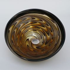Hand blown transparent glass sink for undulating vortex of colors that swirl toward the drain.
