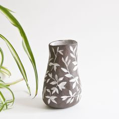 "Hand built vase made of dark brown clay and painted allover with a white leafy pattern. Matte exterior, and glazed inside with a matte white. Holds water, food and drink safe.Vase measures 4.75"" tall with a 2"" diameter across top. 3"" across at widest point.Please note, all of my ceramics are hand built and hand painted and are not perfect"
