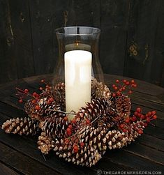 There's such a sweet, timeless feel to this hurricane glass candle holder surrounded by real pine cones and winter berries. #Christmas #winter #pine_cones #candles #wedding #centerpiece #decor #decorations #rustic #country