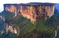Mount Roraima, South America: This tabletop mountain is one of the oldest mountains on Earth, dating back two billion years when the land was lifted high above the ground by tectonic activity. The sides of the mountain are sheer vertical cliffs, with several waterfalls, making it nearly impossible to climb.