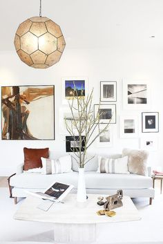 Bright white living space with a gray sofa, tons of throw pillows, and an eclectic gallery wall