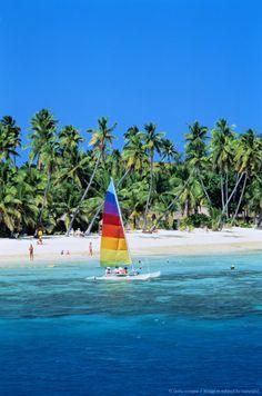 Fiji, Plantation Island, small sailboat off-shore of palm beach
