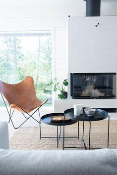 talo markki - scandinavian livingroom interior - log home - leather butterfly chair - black tables #minimalisthomedecor