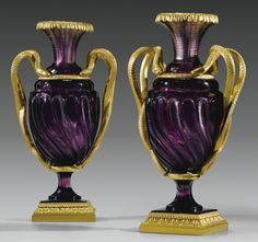 A RARE PAIR OF GILTBRONZE MOUNTED AMETHYST CRYSTAL VASES, IMPERIAL GLASS FACTORY, ST PETERSBURG, CIRCA 1830 the flared neck lobulated cut in horizontal stripes, the shoulder lugs, the belly decorated with twisted channels in striated borders, resting on a pedestal and a circular faceted bronze base decorated with friezes of acanthus leaves and stylized palmettes; the handles in the shape of snakes intertwined gilt bronze