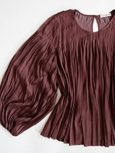 """Flowy pleated satin with intricate smocking, top stitching and detailed pleating along shoulders, gathered cuff, straight back yoke with shirring, center back button closure, 22"""" from shoulder to hem"""
