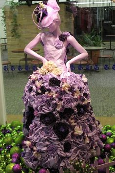 I was drawn to this dress because I like how the fabric was made to create flowers on the skirt. I like how instead of using actual flowers  the designer took time to use the fabric to create roses and flowers. I also like how flowers were used on the hat as well. The flowers create volume in an interesting way rather than just having a really plain full skirt.