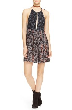 A daring front keyhole and cutaway shoulders make for a summer-perfect silhouette in this lightweight slipdress styled with a slender tie at the shoulder and an artful mixed print by Free People.