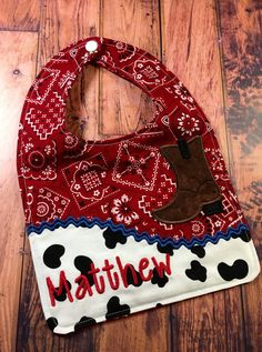 This listing is for one cowboy theme baby bib. This would make a great shower gift or new mommy/grandma gift. The front top is red bandana print with a cow pattern on the bottom. There is an appliquéd cowboy boot. The back is the red bandana print. There is a layer of absorbent flannel in the middle. Please convo me if you would like a different fabric combo. I love custom orders! ;)  The bib measures approximately 7.25 wide by 10 tall. It will fit babies up to about 1 year. (It fits snugly…
