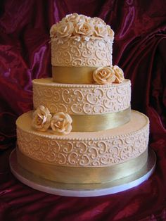 Buttercream in ivory color with gold ribbon and buttercream roses