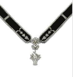 Diamond necklace, Cartier, circa 1915. Millegrain set at intervals with floral and foliate motifs of rose diamonds between similarly set borders, to a central pendant of giardhetto and ribbon design with a flower head surmount millegrain set with circular and rose diamonds mounted onto a black velvet background. Signed Cartier, Paris