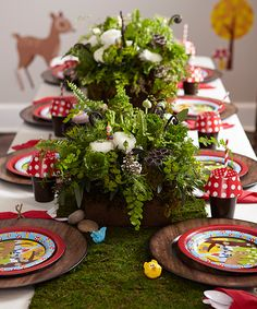 Flower arrangements from a florist minimize decorating time and take on the party theme with the addition of diminutive gnomes. Toy animal tops and river rocks contribute to the effect, and a runner made of moss pulls the entire table together.
