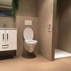 Een badkamer met een wandafwerking d.m.v. microcement.