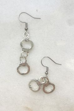 Silver handcuff dangle earrings. Miniature, cute jewelry. Police, FBI, Interpol, Secret Service, Scotland Yard... they all use handcuffs, also use them. But in a more elegant form, to add a touch of crazy to your look. And don't be afraid, it's 100% legal, and even more... desired #handcuffearrings #handcuffaesthetic #handcuffcute #silverhandcuffearrings #doublehandcuffearrings #handcuffcharm #punkearrings #grungeearrings #cutepunk #aestheticgrunge Punk Earrings, Unique Earrings, Statement Earrings, Dangle Earrings, Unique Jewelry, Punk Jewelry, Etsy Jewelry, Grunge Accessories, Secret Service