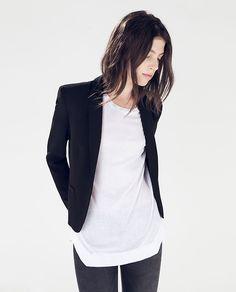 black or dark grey skinny pants, longer white shirt, and black blazer.