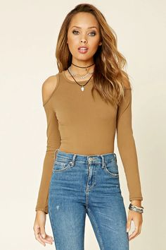 A knit top featuring a scoop neckline and open-shoulder long sleeves.