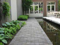 Achter een monumentaal pand in de binnenstad van 's Hertogenbosch hebben wij een tuin gerealiseerd die volledig is afgestemd op de wensen van de opdrachtgever en passend is bij de architectuur van de woning. Een verhoogd terras (waarop de eettafel) van grote Belgische hardstenen platen wordt geflankeerd door een smalle vijver. Achterin de tuin ligt tegen het einde van deze vijver een vlonderpartij met daarop de loungehoek. Tevens bevindt zich hier de in de vlonder ingebouwde whirlpool. De…