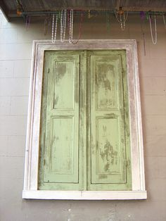 Mardi Gras beads hanging of rod over shuttered window, New Orleans
