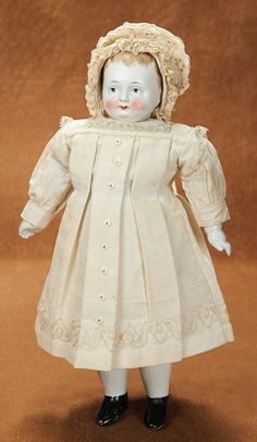 """German Bisque Taufling Baby in Antique Costume  15"""" (38 cm.) Solid domed bisque head with flat-cut neck socket that pivots on shoulder plate neck dowel, muslin midriff with bellows crier,porcelain hips and lower limbs with painted black shoes.Germany,circa 1860,the doll combines rare glazed bisque head with porcelain shoulder plate and limbs that are original."""