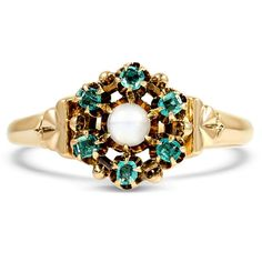A moonstone is surrounded by a halo of emeralds in this decadent 10K yellow gold Victorian ring from the 1900's (Emerald approx. 0.32 total carat weight).