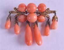 AN ANTIQUE YELLOW GOLD AND CARVED RED CORAL BROOCH. 15.6 grams. 7 cm wide.