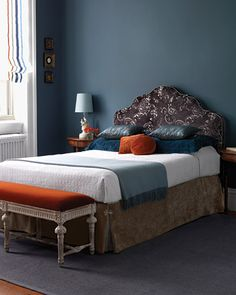 The matte blue wall color and burnt orange look so good together! beautiful bench at the end of the bed too!