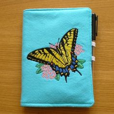 A6 Covered Notebook with Swallowtail Butterfly Embroidery by EmbroideryScene