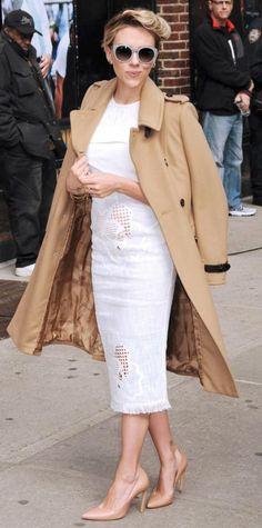 Scarlett Johansson brought her superhero style to the set of The Late Show with David Letterman in a white hibiscus cotton Roland Mouret dress that she styled with a camel coat draped over her shoulders, gray round frames, and nude Roger Vivier pumps.