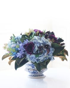 Clusters of handcrafted silk polyester hydrangeas, calla lilies, and poppies sit on a bed of magnolia leaves, complemented by sprigs of pittosporum leaves and lilacs. #MothersDay #GiftIdeas
