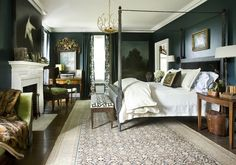 This master bedroom designed by Barbara Westbrook of Westbrook Interiors is dramatic and elegant with its dark wall color, four-poster bed and eye-catching brass chandelier. Seemingly opposing elements are expertly woven together in the space, unified by key pieces with a more traditional feel.