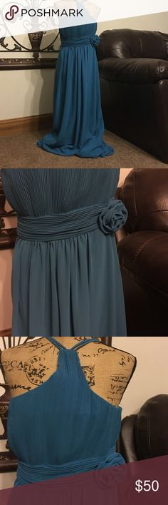 NWT Evening Wear Gown. Size XL New With Tag Dollar Evening Gown provided on JJsHouse. This long flowing floor length gown is proudly made in the USA. Size XL. This beautiful teal color gown is sleek in design. A-line waist band with a beautiful rosette on the front side of the gown. The back zipper enclosure. Perfect for a wedding, a formal dress attire for a ship cruise, a dinner date or just because day. Dresses High Low