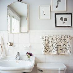 Black-and-white paintings look elegant in a white bathroom.