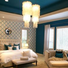Back wall with pattern and solid surrounding walls. White fabric headboard, seating area. Dreamy master bedroom!