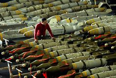 An aviation ordnanceman observes rows of bombs on the hangar bay of the USS Kitty Hawk aircraft carrier in the northern Gulf March 30, 2003. The carriers airwing flew 104 total sorties over Iraq yesterday and dropped bombs on targets including air defence sites, a train loaded with tanks and a surface-to-air missile site.